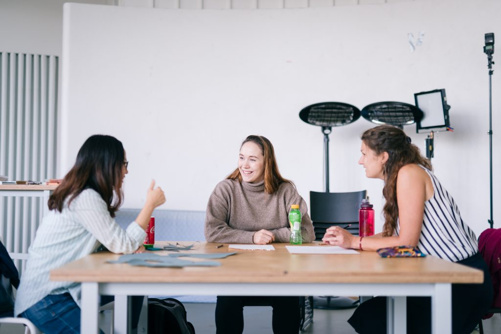 University students discussing in drawing class