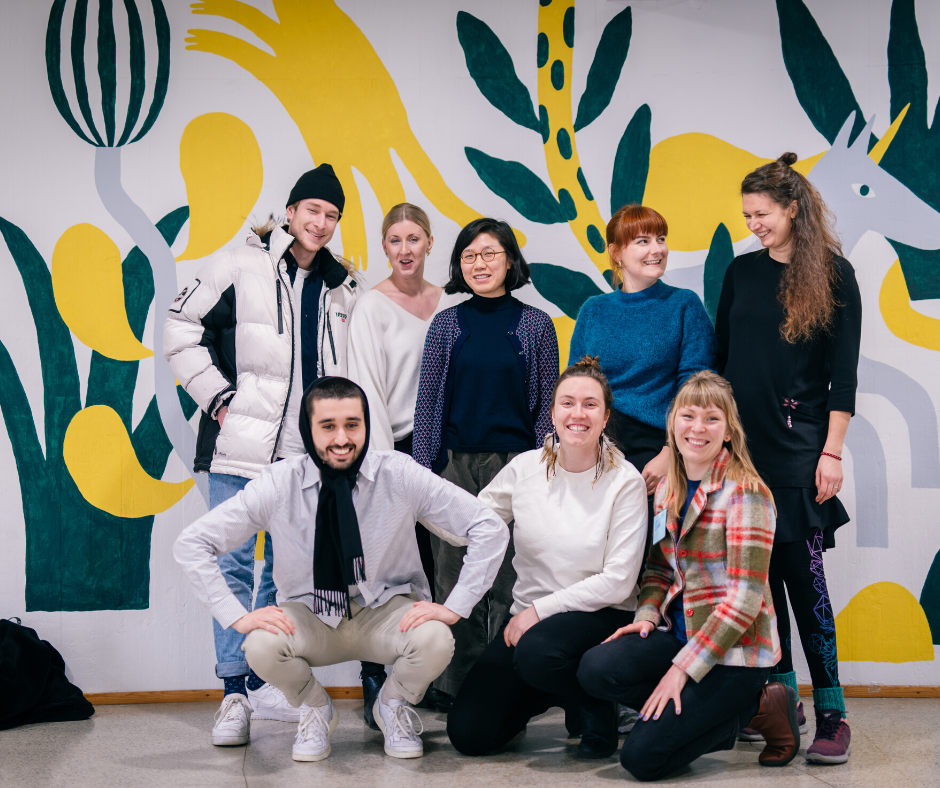 Group picture of 8 students smiling in front of mural painting in Aalto University campus
